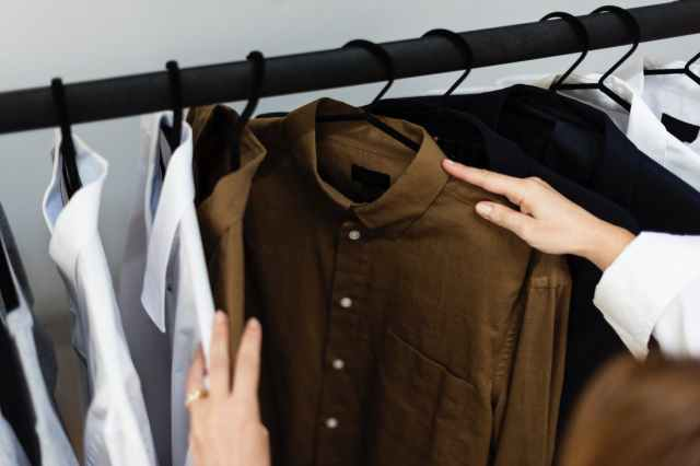 person holding brown dress shirt