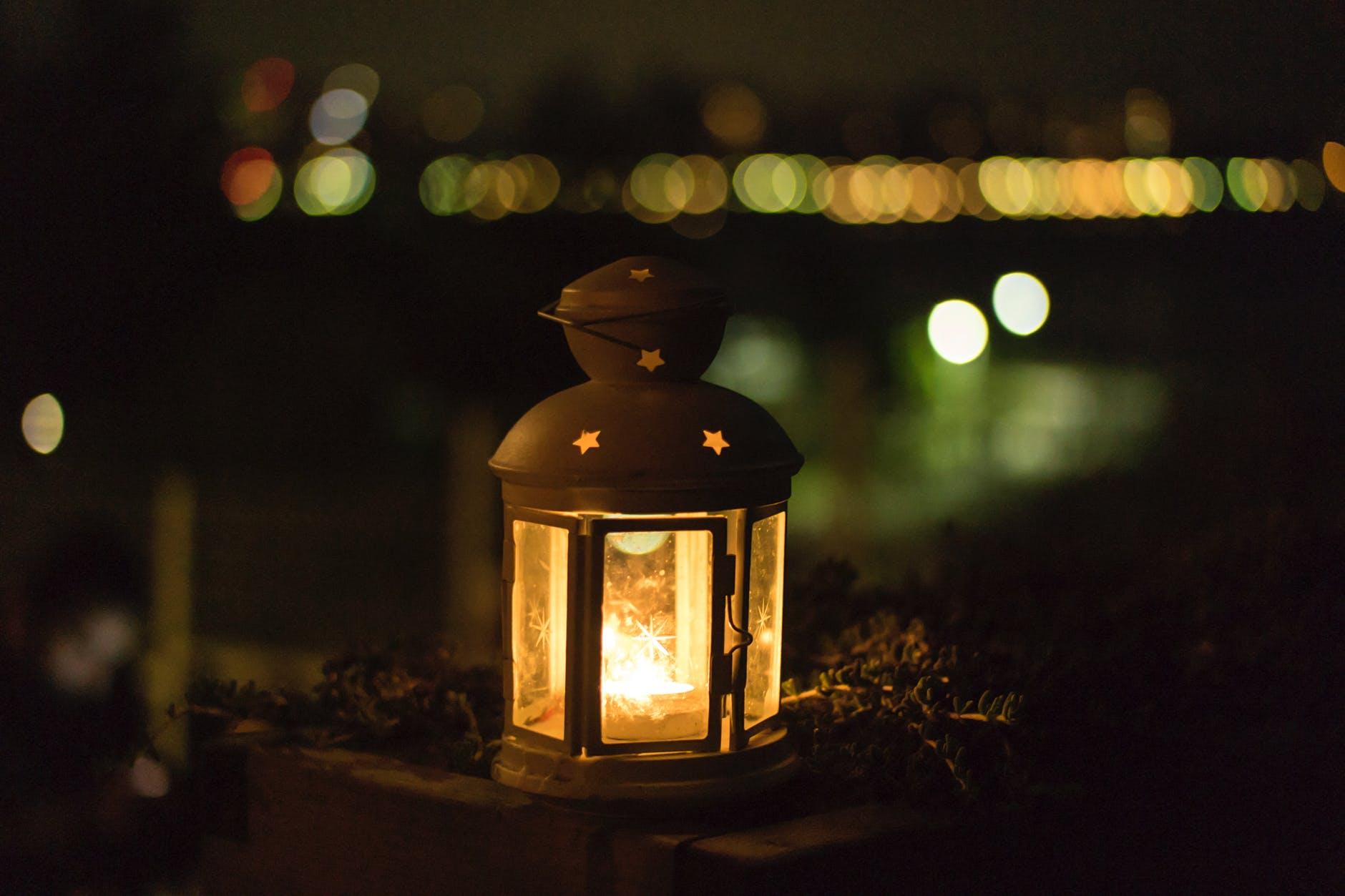 yellow lantern near body of water during night